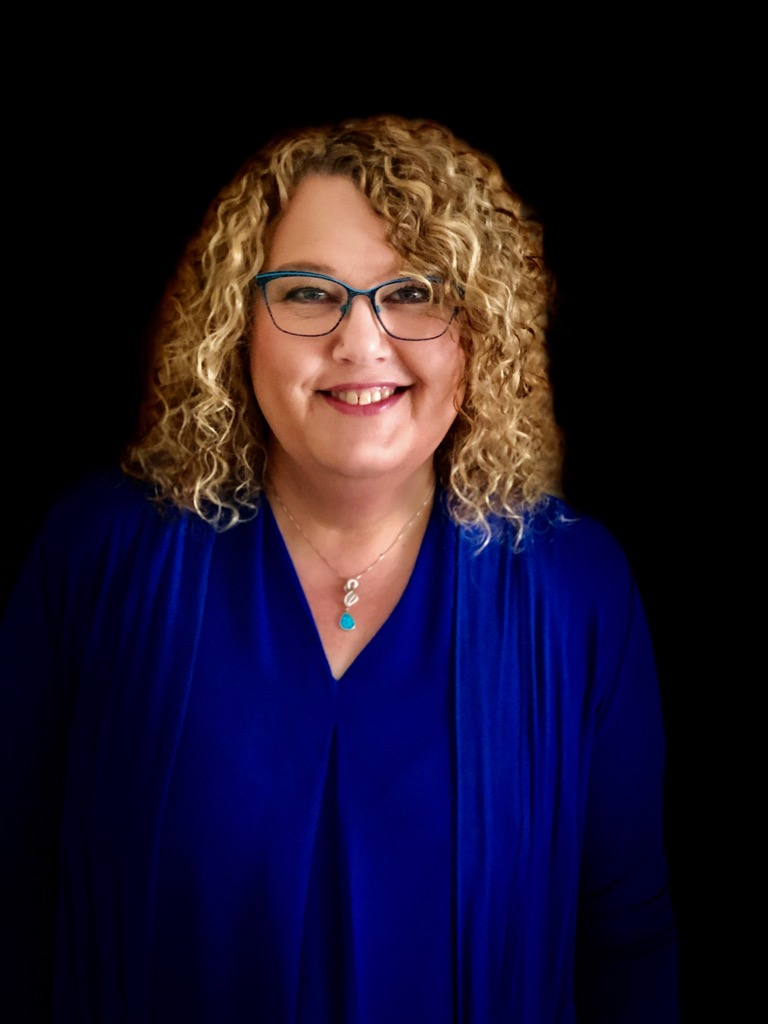 Photo of Beverley Shiels, smiling woman with blonde curly hair and glasses